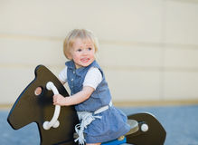 Baby girl swinging on horse on playground Royalty Free Stock Photo