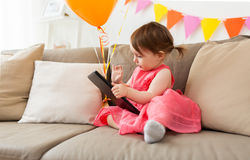 Baby girl with tablet pc on birthday party at home Royalty Free Stock Photo