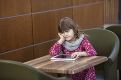 Baby girl with tablet at a table in a cafe, waiting, shopping ce Royalty Free Stock Photo
