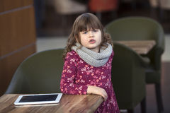 Baby girl with tablet at a table in a cafe, waiting, shopping ce Royalty Free Stock Images