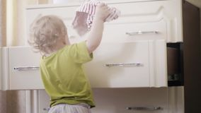 Little baby girl picks her clothes out of the dresser royalty free stock images