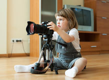 Baby girl takes photo with camera Stock Photos