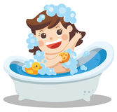 A baby girl taking a bath in bathtub with lot of soap lather and. Rubber duck Stock Photos