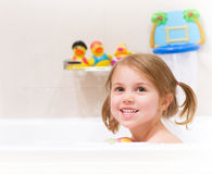 Baby girl taking bath. Cute happy baby girl taking bath with foam and toys, child's hygiene, healthy lifestyle, carefree childhood concept Stock Image