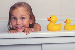 Baby girl taking bath with foam and toys. Cute happy baby girl taking bath with foam and toys, child`s hygiene, healthy lifestyle, carefree childhood concept royalty free stock photography