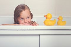 Baby girl taking bath with foam and toys. Cute happy baby girl taking bath with foam and toys, child`s hygiene, healthy lifestyle, carefree childhood concept stock photography