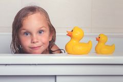 Baby girl taking bath with foam and toys. Cute happy baby girl taking bath with foam and toys, child`s hygiene, healthy lifestyle, carefree childhood concept royalty free stock image