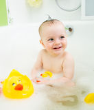 Baby girl taking bath and playing toys Stock Images