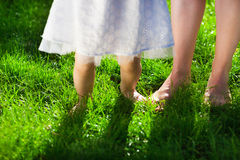 Baby girl taking first steps with mother help. In summer garden stock images