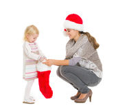 Baby girl taking out present from Christmas sock Royalty Free Stock Images
