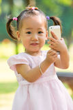 Baby girl taking photo by mobile Royalty Free Stock Photography