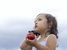 Baby girl  talking on a cellphone. Baby girl holding an apple whilst talking on a cellphone Stock Image