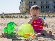 Baby girl tasting sand on beach Stock Photography