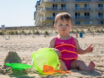 Baby girl tasting sand on beach Royalty Free Stock Images