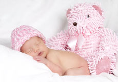 Baby girl with teddy bear. A young baby girl lies on a fluffy white pillow with a pink hat and pink teddy bear stock photo