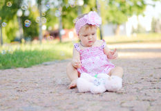 Baby girl with teddy bear. Baby girl in a pink dress with teddy bear sitting in the park royalty free stock photo