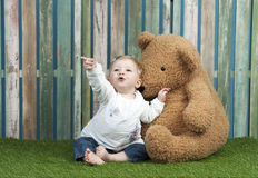 Baby girl with teddy bears seated on grass Royalty Free Stock Photos