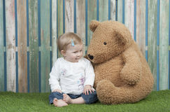Baby girl with teddy bears seated on grass Royalty Free Stock Photography