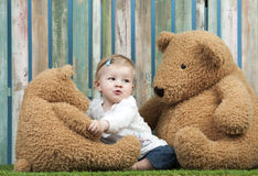 Baby girl with teddy bears seated on grass Stock Images