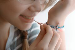 Baby girl with teeth tying the bracelet on her hand close up Royalty Free Stock Photo