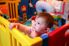 Baby girl thinking in a playpen. Baby girl thinking in a colourful playpen Royalty Free Stock Image