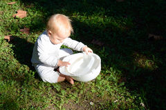 Baby girl thoroughly examines the hard cap. A baby girl thoroughly examines the constructuion hard cap Stock Photos