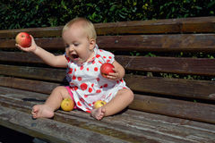 A baby girl throwing apples to the ground Stock Images