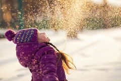 Baby girl throws the snow in frosty winter park. Flying Snowflakes. Sunny day. Child to have fun outdoors stock photography