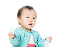 Baby girl with tissue on hand Stock Image