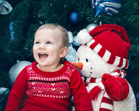 Baby girl toddler with blue eyes in red dress sitting  by New Year tree  near snowman toy Stock Image