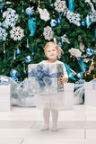 Baby girl toddler in white dress clothes with gift present box by New Year tree. Portrait of happy funny smiling blonde Caucasian baby girl toddler in white stock photography