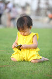 A baby girl touch screen her smartphone on lawn Stock Photography