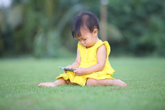 A baby girl touch screen her smartphone on lawn Stock Images