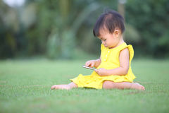 A baby girl touch screen her smartphone on lawn Royalty Free Stock Photography