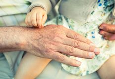 Baby girl touching hand of senior man Royalty Free Stock Photography