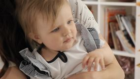Baby girl touchs her mom`s hair hugged by her parents slow motion stock video footage