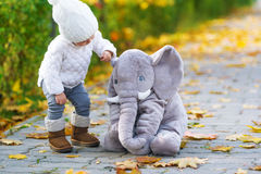 The baby girl and toy elephant are in the autumn city park. Stock Images