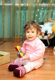 Baby girl with toy on floor Stock Images
