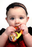 Baby girl with toy in mouth Royalty Free Stock Photos