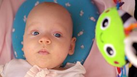 Baby girl with toy in pram. Portrait of lovely blue-eyed three months baby girl lying in baby carriage with green toy stock video