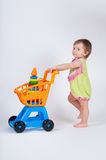 Baby girl with toy shopping cart. Isolated on white background. Royalty Free Stock Photography