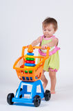 Baby girl with toy shopping cart. Isolated on white background. Stock Image