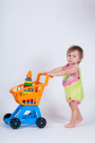 Baby girl with toy shopping cart. Isolated on white background. Royalty Free Stock Image