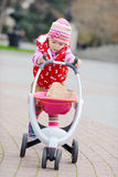 Baby girl with toy stroller Royalty Free Stock Photos