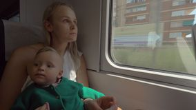 Baby girl traveling with mum by train. Mum with child in the train riding through the city. Woman holding child on the lap and kissing her head. Family travel stock footage