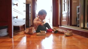 Baby girl trying put on shoes sitting over wooden. Curious baby girl trying put on different shoes sitting over a wooden floor at home stock footage