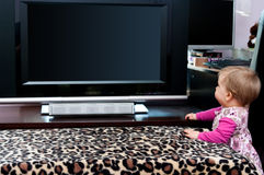 Baby girl and TV Royalty Free Stock Image