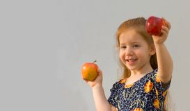 Baby girl with two apples (Focus on yellow apple). Girl holding two apples Рred and yellow Royalty Free Stock Images
