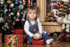 Baby girl under the Christmas tree Stock Photos