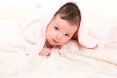 Baby girl under hidden pink blanket on white fur. Baby girl under hidden pink blanket on winter white fur background Royalty Free Stock Photo